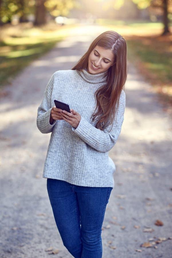 Νέα γυναίκα brunette στο γκρίζο πουλόβερ και τζιν παντελόνι που χρησιμοποιούν το μεγάλο smartphone στοκ εικόνες
