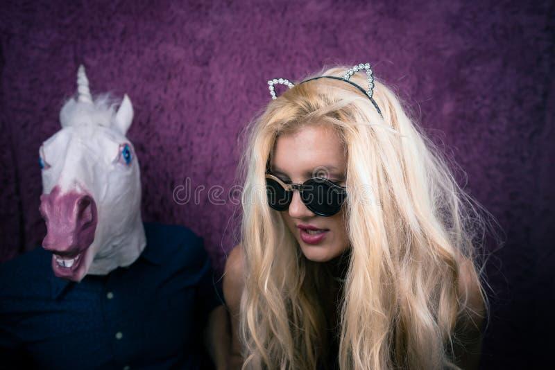Νέα γυναίκα Freaky στα γυαλιά ηλίου και τα αυτιά γατακιών που φιλά τον ευτυχή μονόκερο στοκ εικόνα