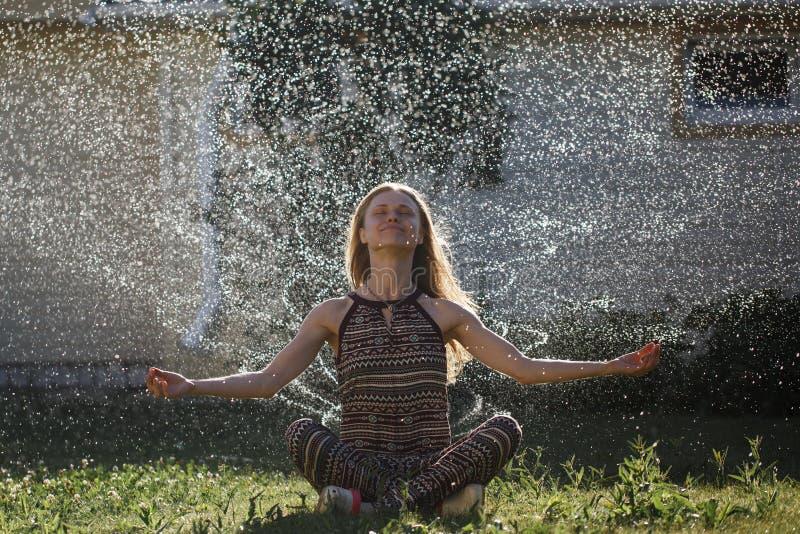 Νέα γυναίκα freshens επάνω κάτω από τα φωτεινά waterdrops στοκ εικόνα