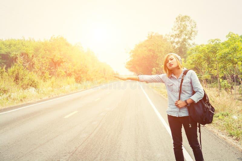 Νέα γυναίκα hipster που κάνει ωτοστόπ στο δρόμο επαρχίας στοκ φωτογραφία