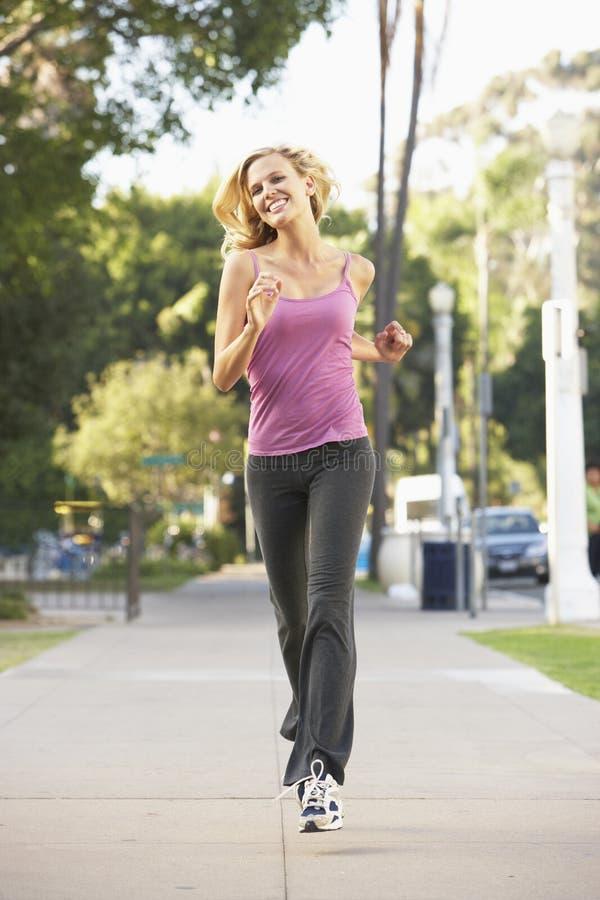 Νέα γυναίκα Jogging στην οδό στοκ εικόνα με δικαίωμα ελεύθερης χρήσης