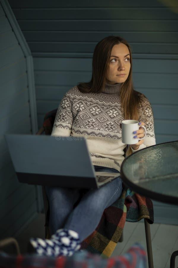 Νέα γυναίκα, lap-top, μπαλκόνι, φλυτζάνι του τσαγιού, φύση στοκ εικόνα