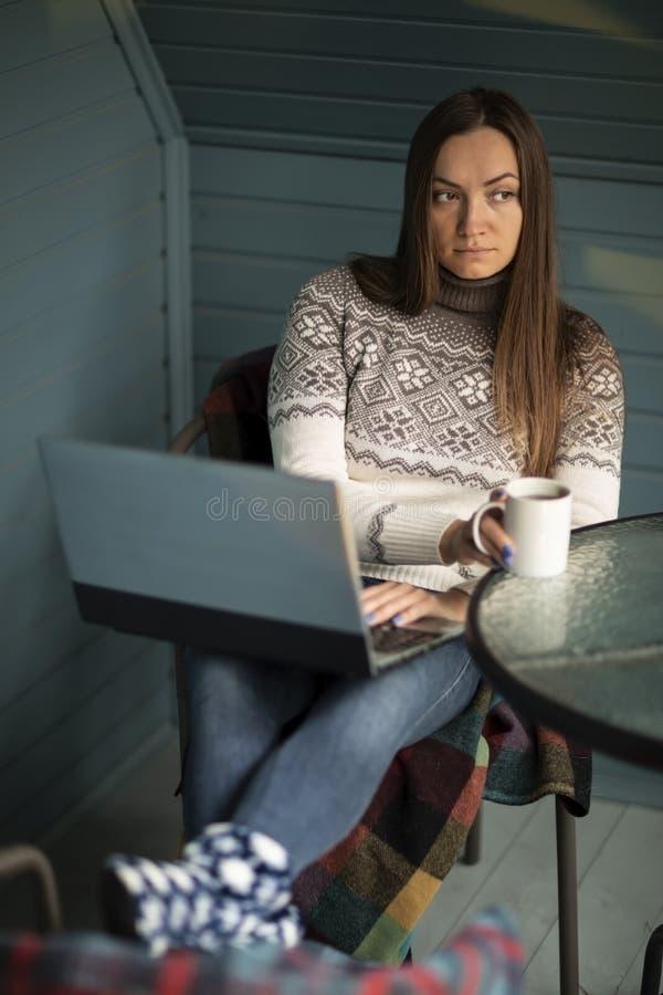Νέα γυναίκα, lap-top, μπαλκόνι, φλυτζάνι του τσαγιού, φύση στοκ φωτογραφίες
