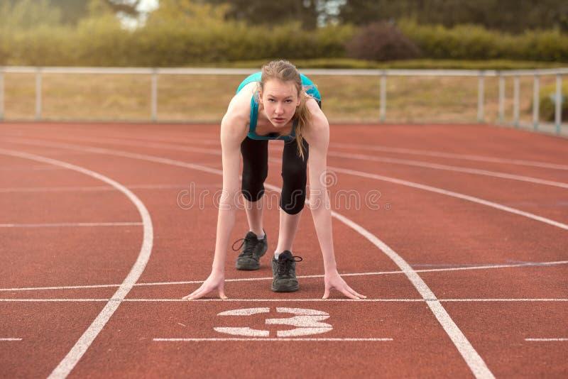 Νέα γυναίκα sprinter στη θέση εκκινητών στοκ εικόνες με δικαίωμα ελεύθερης χρήσης