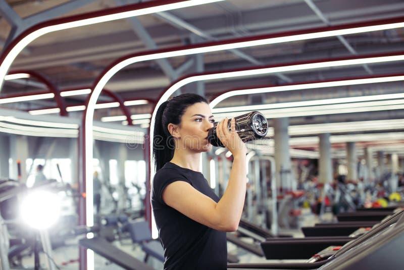 Νέα γυναίκα treadmill στο πόσιμο νερό στοκ εικόνα με δικαίωμα ελεύθερης χρήσης