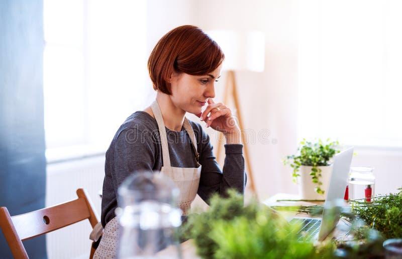 Νέα δημιουργική γυναίκα σε ένα ανθοπωλείο, που χρησιμοποιεί το lap-top Ένα ξεκίνημα της επιχείρησης ανθοκόμων στοκ εικόνες