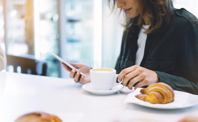 Νέα εκμετάλλευση γυναικών στο θηλυκά κινητά τηλέφωνο και το ποτό χεριών καυτός καφές αρώματος ή τσάι στο χρόνο προγευμάτων, hipst στοκ εικόνα