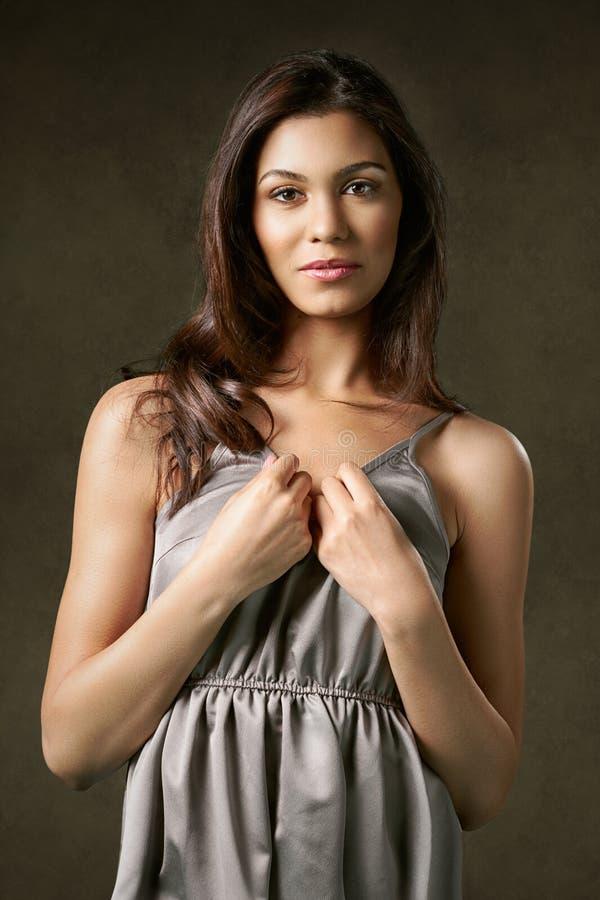 Νέα, ελκυστική, αισθησιακή γυναίκα σε ένα ασημένιο φόρεμα νύχτας στοκ εικόνα