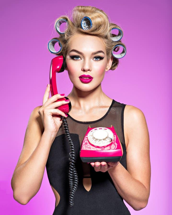 Νέα ελκυστική γυναίκα με τα μπλε culers που χρησιμοποιεί ένα παλαιό τηλέφωνο στοκ εικόνα με δικαίωμα ελεύθερης χρήσης