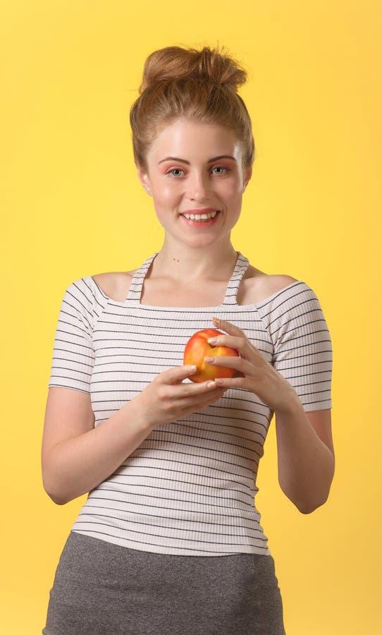 Νέα ελκυστική γυναίκα με το λευκό σαν το χιόνι χαμόγελο που κρατά το κόκκινο μήλο στοκ εικόνες