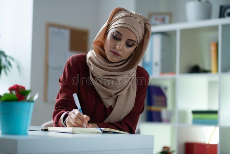 Νέα ελκυστική γυναίκα με το φυσικό makeup που κάνει μερικές σημειώσεις στοκ εικόνες