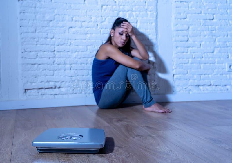Νέα ελκυστική γυναίκα που βασανίζεται με το βάρος που εξετάζει την κλίμακα στοκ εικόνες