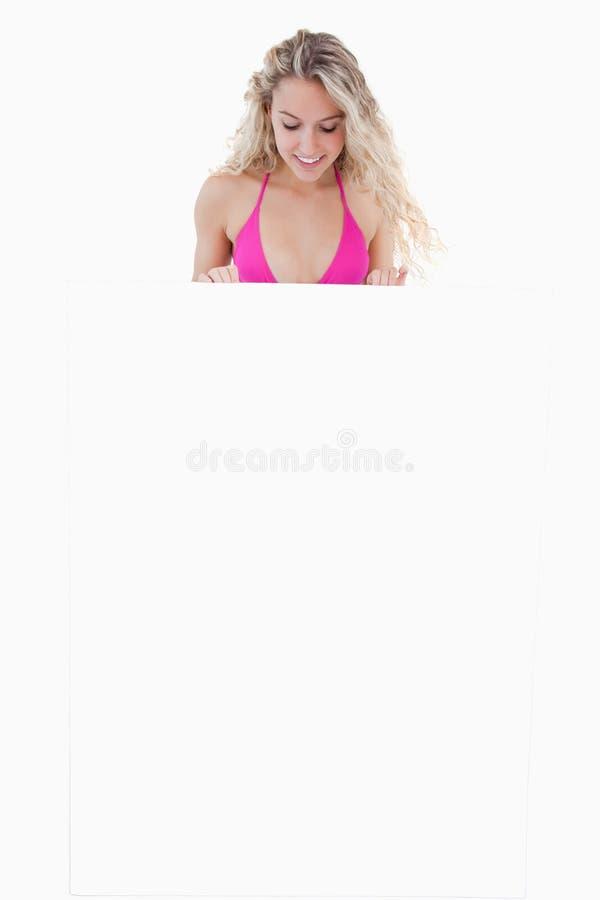 Νέα ελκυστική γυναίκα που εξετάζει την κενή αφίσα της στοκ φωτογραφίες