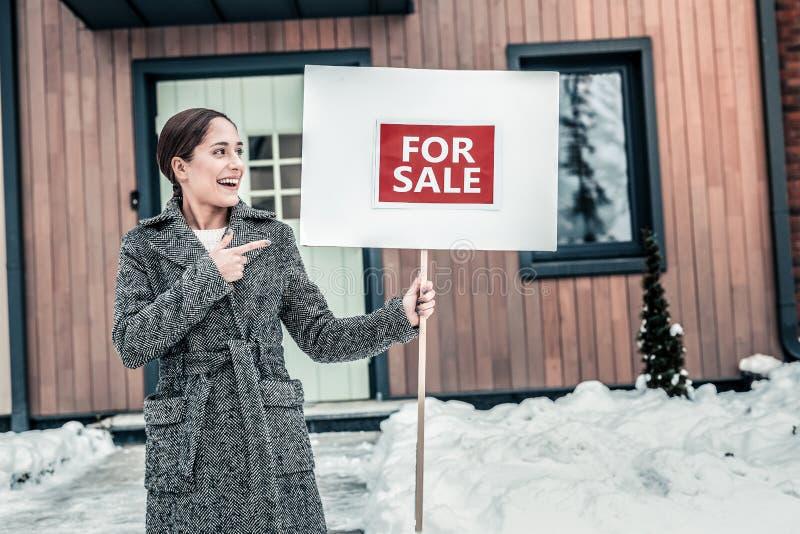 Νέα ελκυστική γυναίκα που φορά το θερμό γκρίζο πωλώντας σπίτι παλτών στοκ φωτογραφία