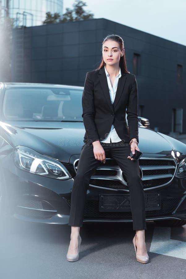 Νέα ελκυστική γυναίκα στη συνεδρίαση κοστουμιών σε μια κουκούλα του Μαύρου στοκ εικόνες με δικαίωμα ελεύθερης χρήσης