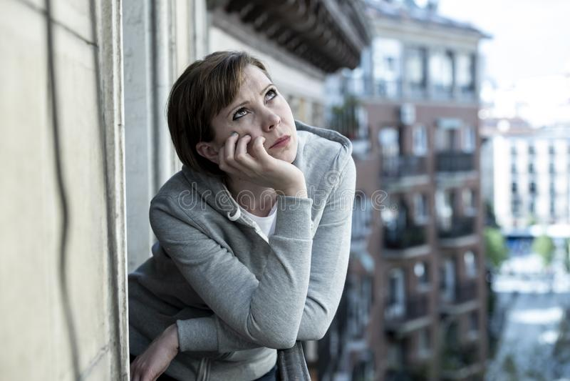 Νέα ελκυστική δυστυχισμένη καταθλιπτική μόνη γυναίκα που φαίνεται ανησυχημένη στο μπαλκόνι στο σπίτι Αστική όψη στοκ εικόνα με δικαίωμα ελεύθερης χρήσης
