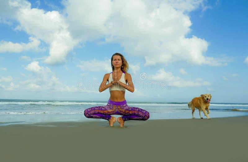 Νέα ελκυστική και αθλητική γυναίκα στη στάση λωτού γιόγκας και namaste τη θέση χεριών στην όμορφη παραλία που κάνει τη χαλάρωση κ στοκ εικόνα με δικαίωμα ελεύθερης χρήσης