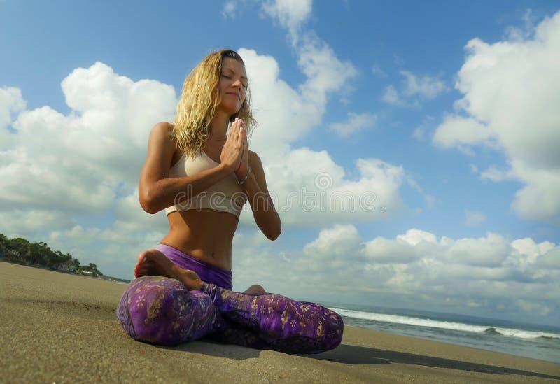 Νέα ελκυστική και αθλητική συνεδρίαση γυναικών στη στάση λωτού γιόγκας και namaste θέση χεριών στην όμορφη παραλία που κάνει τη χ στοκ εικόνα με δικαίωμα ελεύθερης χρήσης