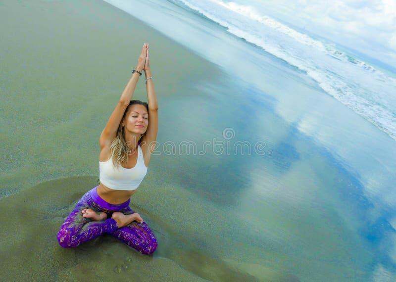Νέα ελκυστική και αθλητική συνεδρίαση γυναικών στη στάση λωτού γιόγκας και namaste θέση χεριών στην όμορφη παραλία που κάνει τη χ στοκ εικόνες
