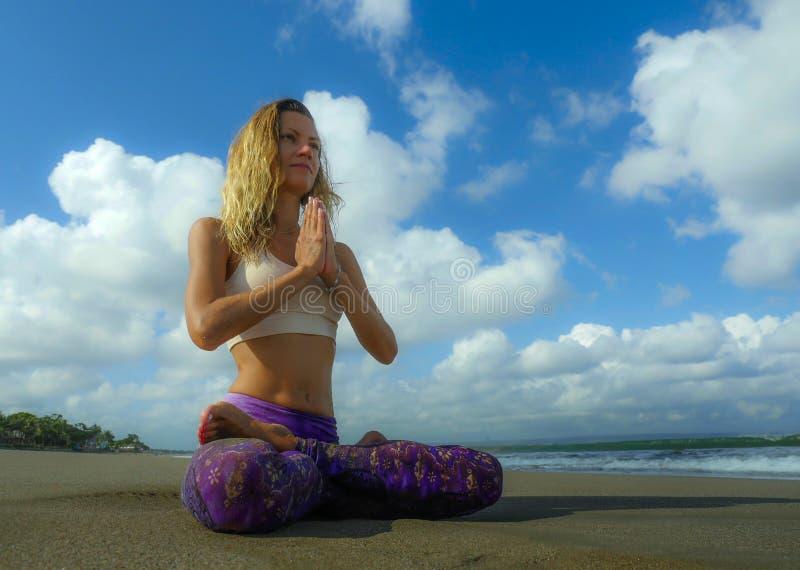 Νέα ελκυστική και αθλητική συνεδρίαση γυναικών στη στάση λωτού γιόγκας και namaste θέση χεριών στην όμορφη παραλία που κάνει τη χ στοκ εικόνες με δικαίωμα ελεύθερης χρήσης