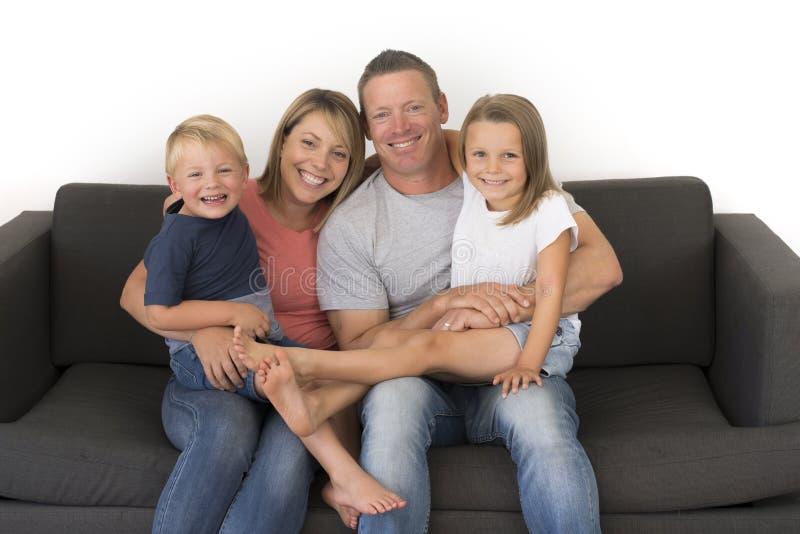 Νέα ελκυστική και ευτυχής τοποθέτηση ζευγών που κάθεται στο σπίτι τον καναπέ ομο στοκ φωτογραφίες με δικαίωμα ελεύθερης χρήσης