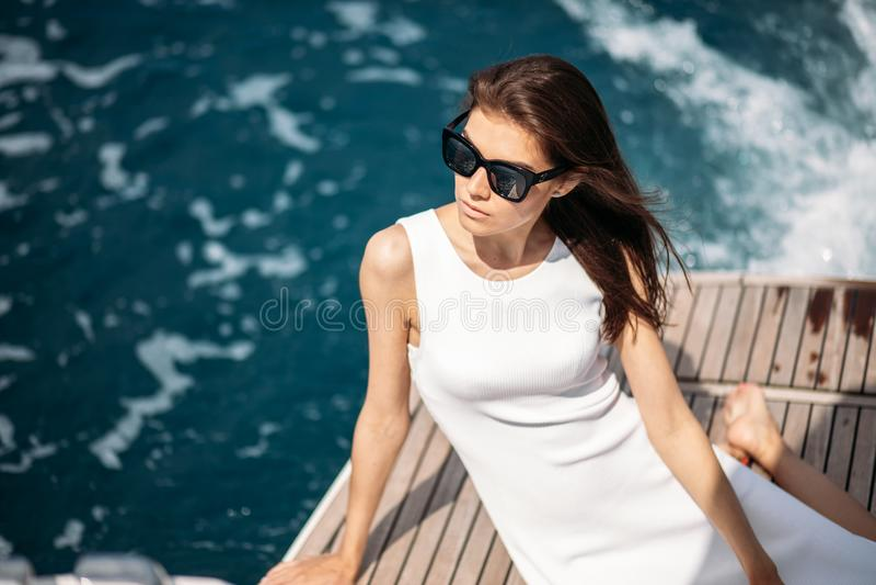 Νέα, ελκυστική και πλούσια γυναίκα που έχει το fotossesion σε μια βάρκα πολυτέλειας στη θάλασσα στοκ φωτογραφία