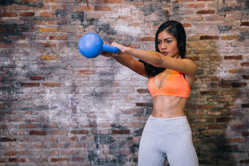 Νέα ελκυστική μυϊκή γυναίκα αθλητών sportswear που ασκεί crossfit workout με το κουδούνι κατσαρολών πέρα από το τούβλινο υπόβαθρο στοκ εικόνα με δικαίωμα ελεύθερης χρήσης