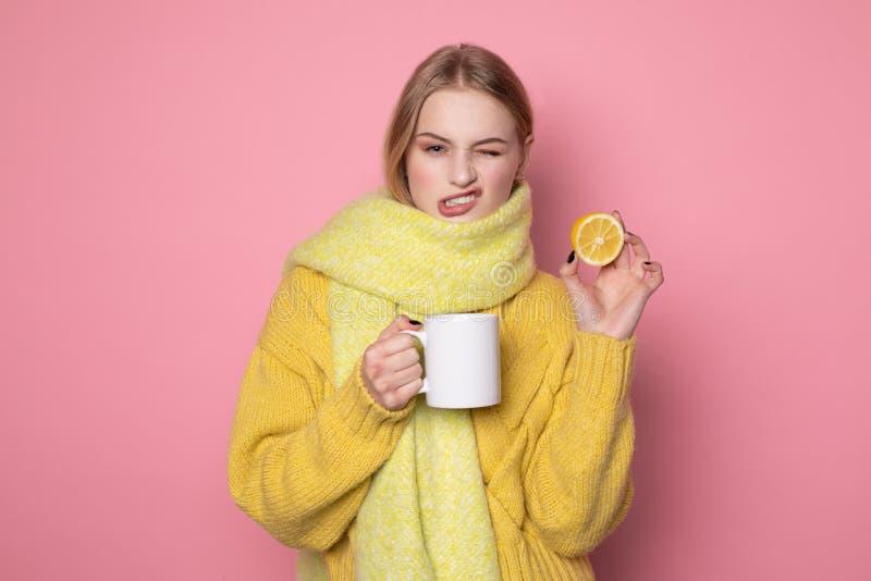 Νέα ελκυστική ξανθή γυναίκα στο κίτρινο πουλόβερ και μαντίλι που κάνει το αστείο πρόσωπο στοκ εικόνες