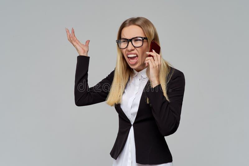 Νέα ελκυστική ξανθή επιχειρησιακή κυρία σε έναν παροξυσμό που κυματίζει τα χέρια της κατά τη διάρκεια ενός τηλεφωνήματος και μιας στοκ φωτογραφίες