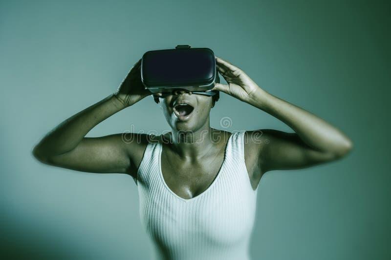 Νέα ελκυστική περίεργη μαύρη αμερικανική γυναίκα afro που φορά τα τρισδιάστατα προστατευτικά δίοπτρα οράματος VR που απολαμβάνουν στοκ εικόνες