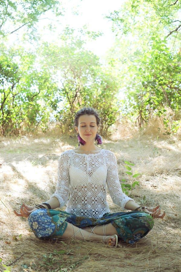 Νέα ελκυστική συνεδρίαση γυναικών meditate στο δάσος στοκ εικόνα