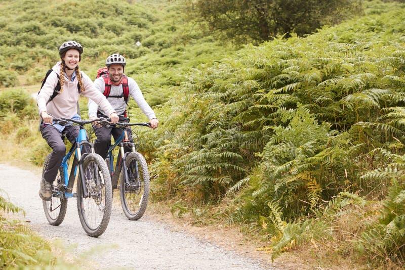 Νέα ενήλικα ποδήλατα βουνών ζευγών οδηγώντας στην επαρχία, πλήρες μήκος στοκ εικόνες