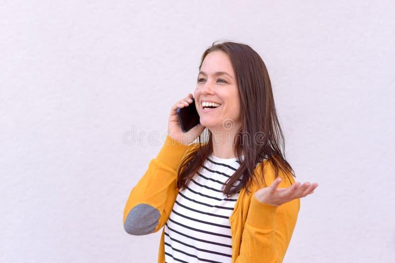 Νέα ενθουσιώδης γυναίκα που χρησιμοποιεί το κινητό τηλέφωνο στοκ φωτογραφία με δικαίωμα ελεύθερης χρήσης