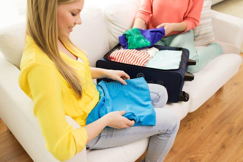 Νέα ενδύματα συσκευασίας γυναικών στην τσάντα ταξιδιού στοκ φωτογραφίες