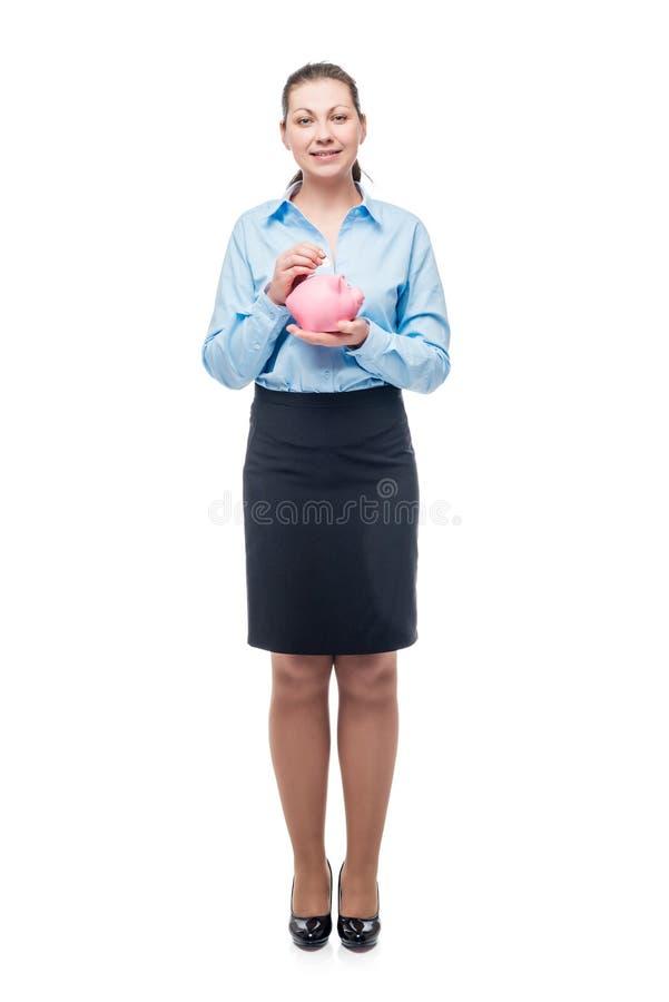 Νέα επιτυχής επιχειρηματίας με μια ρόδινη piggy τράπεζα σε ένα λευκό στοκ εικόνες