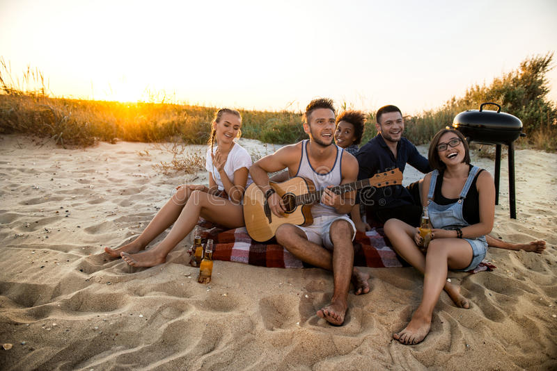 Νέα επιχείρηση των φίλων που χαίρονται, που στηρίζεται για την παραλία κατά τη διάρκεια της ανατολής στοκ φωτογραφία με δικαίωμα ελεύθερης χρήσης