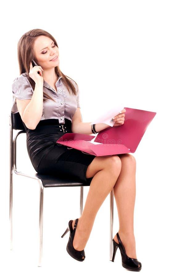 Νέα επιχειρηματίας με το τηλέφωνο στην καρέκλα στοκ εικόνες