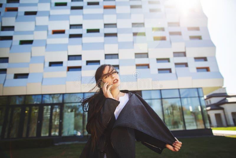 Νέα επιχειρηματίας που μιλά στο κινητό τηλέφωνο κατά τη διάρκεια του υπαίθριου διαλείμματος, κοντά στο κτίριο γραφείων r στοκ φωτογραφίες με δικαίωμα ελεύθερης χρήσης