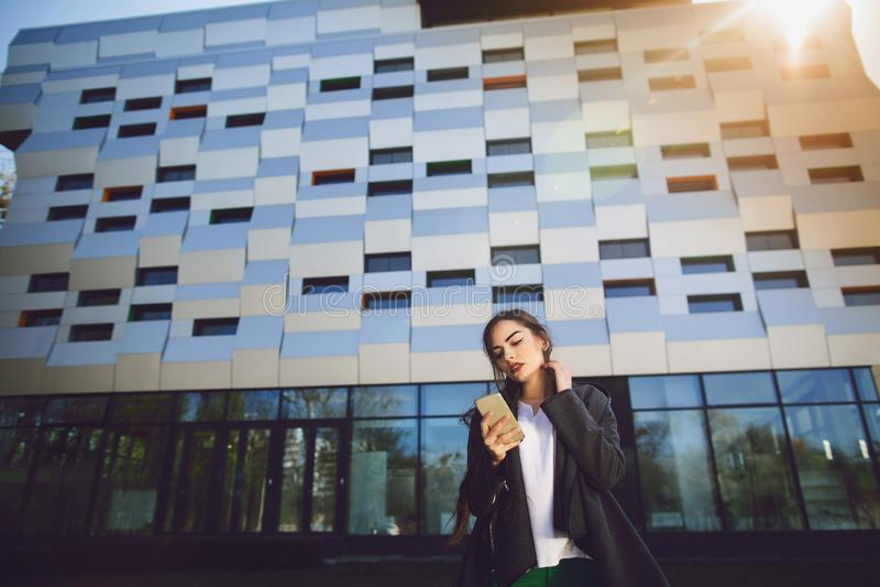 Νέα επιχειρηματίας που μιλά στο κινητό τηλέφωνο κατά τη διάρκεια του υπαίθριου διαλείμματος, κοντά στο κτίριο γραφείων Έννοια επι στοκ εικόνα με δικαίωμα ελεύθερης χρήσης