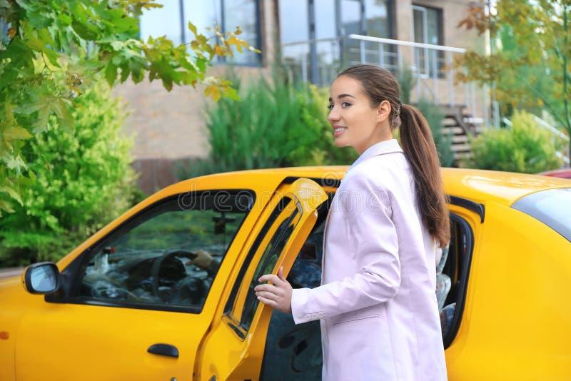 Νέα επιχειρηματίας που παίρνει στο ταξί στοκ εικόνες
