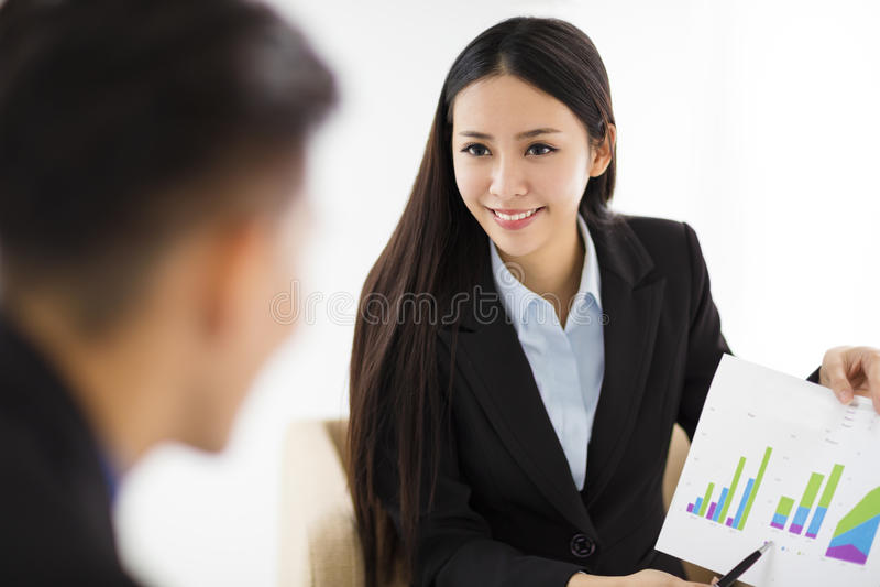 Νέα επιχειρηματίας που παρουσιάζει γραφική παράσταση στο διάγραμμα στην αρχή στοκ εικόνες