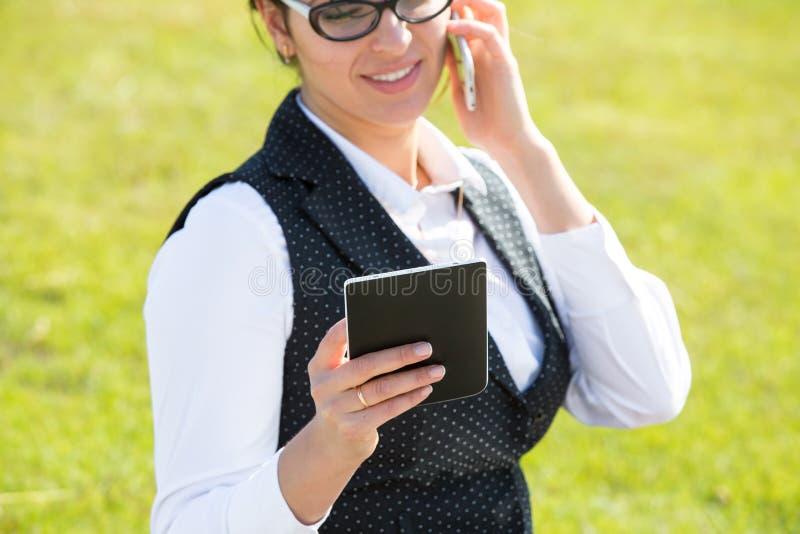 Νέα επιχειρησιακή γυναίκα με την ταμπλέτα και το τηλέφωνο στοκ φωτογραφίες