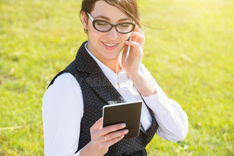 Νέα επιχειρησιακή γυναίκα με την ταμπλέτα και το τηλέφωνο στοκ εικόνες με δικαίωμα ελεύθερης χρήσης