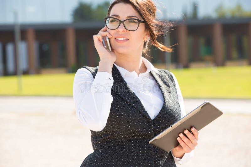 Νέα επιχειρησιακή γυναίκα με την ταμπλέτα και το τηλέφωνο στοκ φωτογραφία