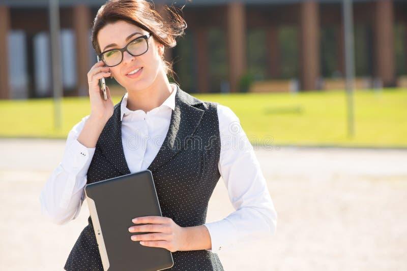 Νέα επιχειρησιακή γυναίκα με την ταμπλέτα και το τηλέφωνο στοκ εικόνες