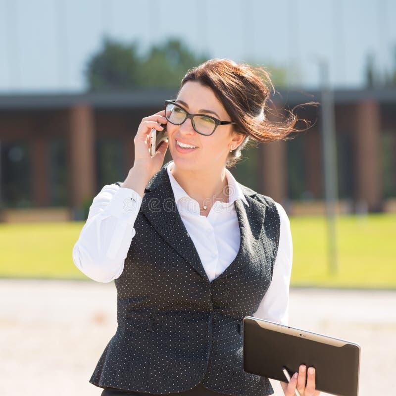 Νέα επιχειρησιακή γυναίκα με την ταμπλέτα και το τηλέφωνο στοκ εικόνα