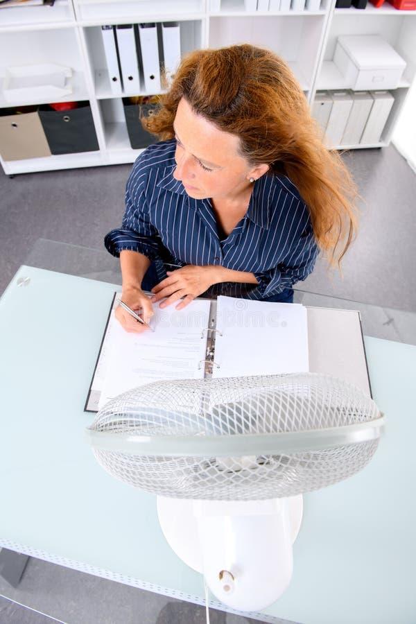 Νέα επιχειρησιακή γυναίκα με τον εξαεριστήρα στο γραφείο του summerly σε καυτό στοκ φωτογραφίες με δικαίωμα ελεύθερης χρήσης