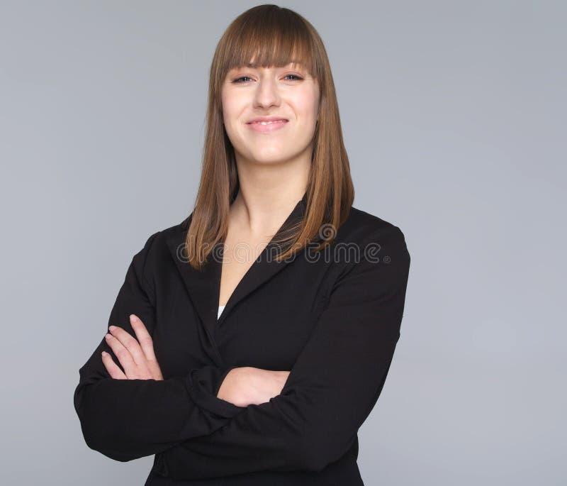 Νέα επιχειρησιακή γυναίκα που απομονώνεται στο γκρίζο υπόβαθρο στοκ φωτογραφίες