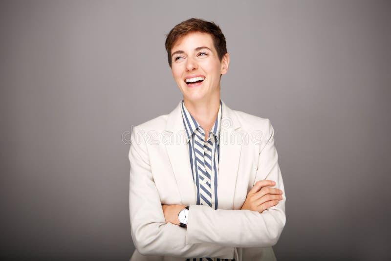 Νέα επιχειρησιακή γυναίκα που γελά στο γκρίζο κλίμα στοκ φωτογραφίες