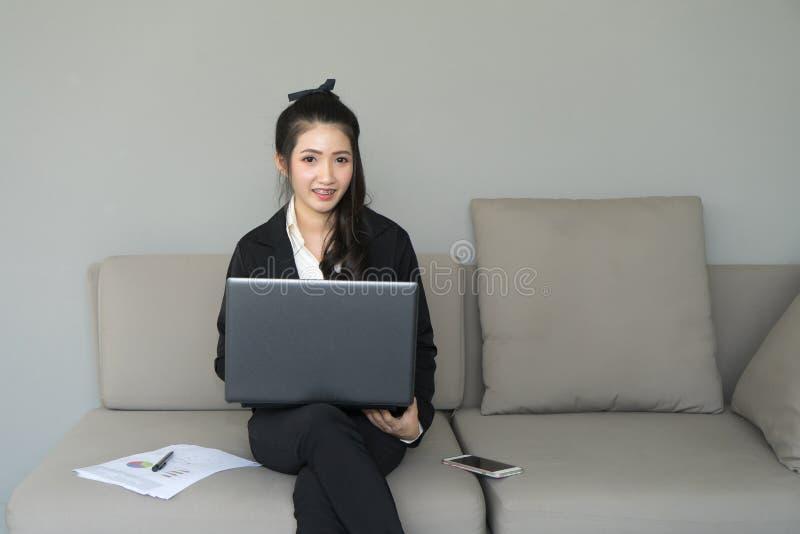 Νέα επιχειρησιακή γυναίκα που εργάζεται με το lap-top και το έγγραφο στον καναπέ κορίτσι στοκ εικόνες